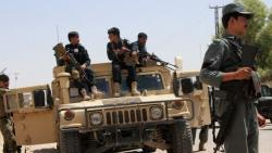 Afghan security personnel sit on atop an armoured vehicles amid an ongoing battle with Taliban militants
