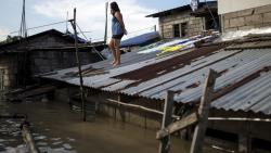 A woman looks on from the roof of her house over floodwaters in the aftermath of Super Typhoon Mangkhut in Calumpit, Bulacan on Monday.