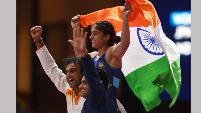 Vinesh Phogat (R) holds up her national flag as she celebrates with his coach after beating Japan's Yuki Irie for the women's wrestling freestyle 50kg gold medal at the 2018 Asian Games in Jakarta on Monday.