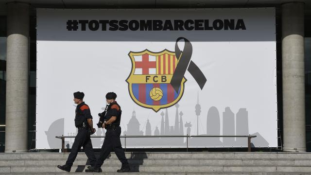 """Armed Catalan policemen, known as Mosso d'Esquadra pass by the FC Barcelona logo with a black ribbon and a message reading """"We are all Barcelona"""" before the Spanish league footbal match FC Barcelona vs Real Betis at the Camp Nou stadium in Barcelona on A"""