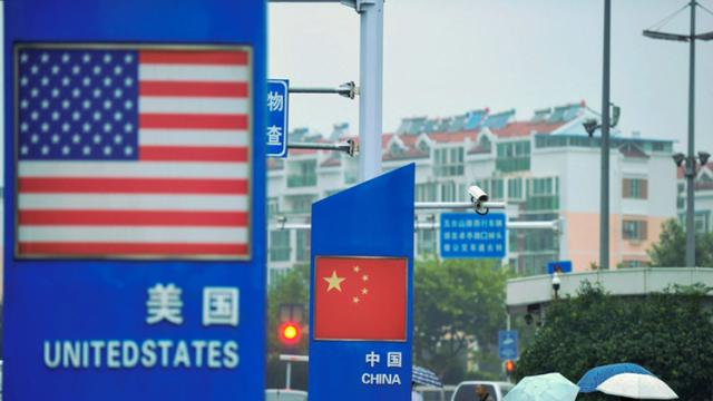 Signs with the US flag and Chinese flag are seen outside a store selling foreign goods in Qingdao in China's eastern Shandong province on Wednesday.