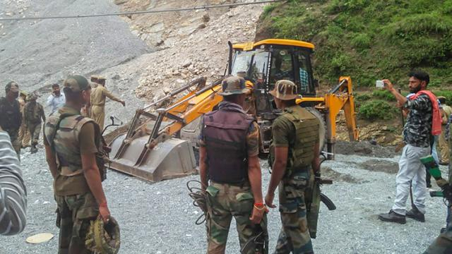 Army personnel at the site where a boulder rolled down and hit people bathing in a waterfall in Reasi district of Jammu and Kashmir on Sunday.