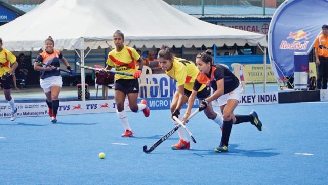 A match in progress between Hockey Maharashtra (in blue) and Hockey Karnataka.