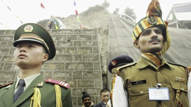 A file photo of a Chinese soldier (L) and an Indian soldier maintaining ceremonial positions marking the international boundary of their countries in Sikkim.