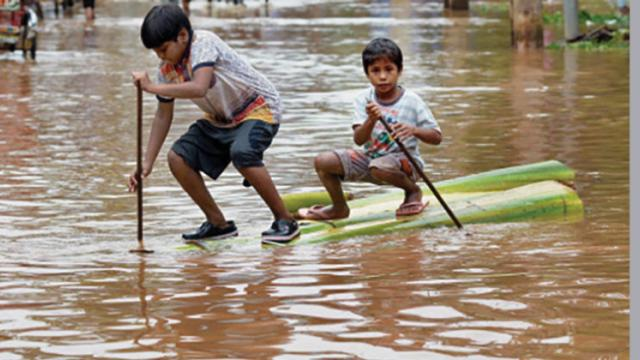 Children neogiate through flood waters in Mizoram.