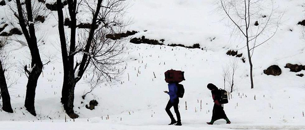 Poonch: People walk on the snow-covered Mughal Road after snowfall in Poonch district.