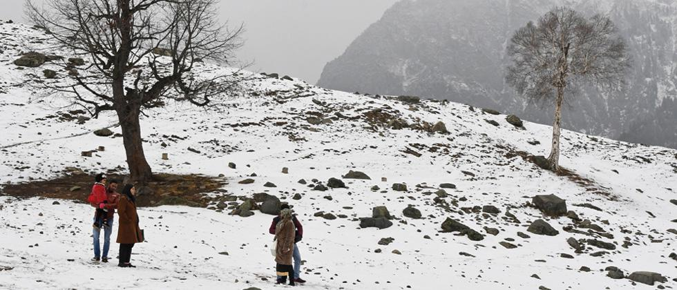 Indian tourists walk after the first snowfall in Sonamarg, 89 kms from Srinagar.