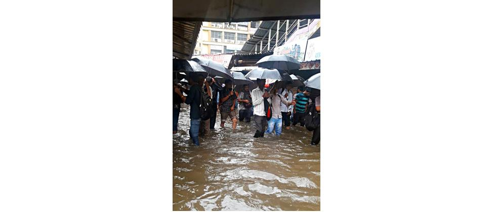 People wade through a waterlogged street after heavy rainfall at Thane Railway Station