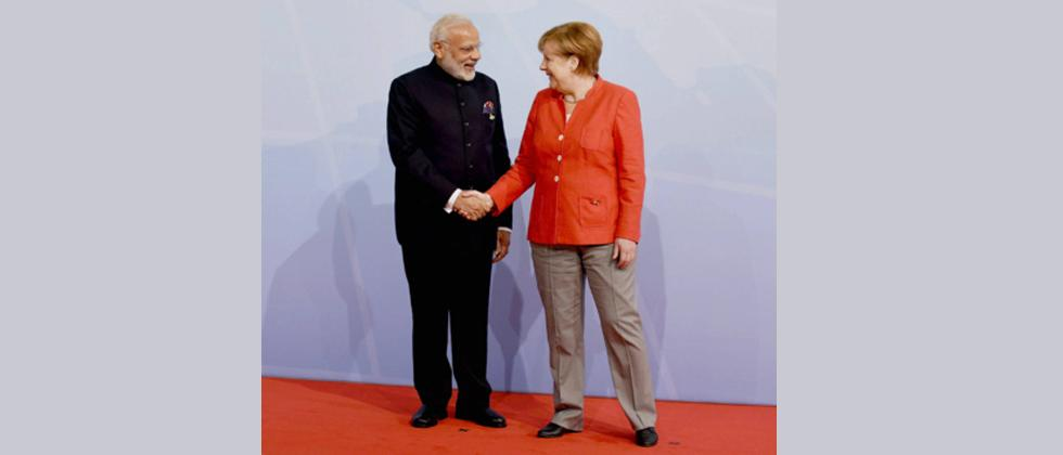 German Chancellor Angela Merkel welcomes India's Prime Minister Narendra Modi as he arrives to attend the G20 summit in Hamburg, northern Germany, on July 7, 2017.