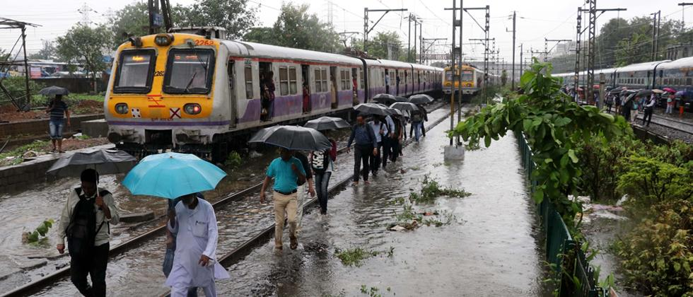 Railway commuters of Central Railway walk through railway track from Kurla to Sion after several local trains services were cancelled and delayed due to heavy rain on early morning on Monday.