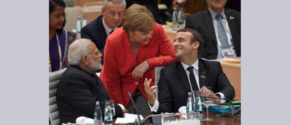 (L to R) India's Prime Minister Narendra Modi, German Chancellor Angela Merkel and French President Emmanuel Macron talk ahead a working session on the first day of the G20 summit in Hamburg, northern Germany.