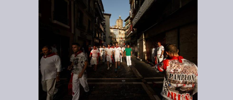 Revellers walk the street after the bull run on the first day of the San Fermin bull run festival in Pamplona, northern Spain on July 7, 2017