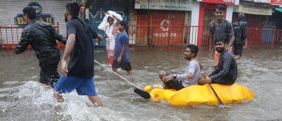 A man uses a inflated boat to cross a water logged street following heavy monsoon showers in Mumbai
