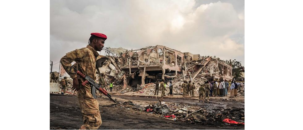 Somali soldiers patrol on the scene of the explosion of a truck bomb in the centre of Mogadishu, on October 15, 2017.