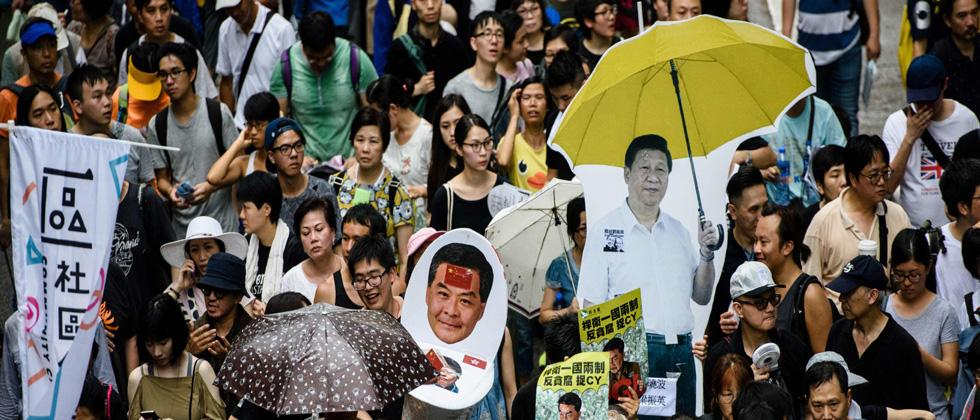 An artwork (C) resembling a toilet with pictures of Hong Kong's former chief executive Leung Chun-ying (top) and new Chief Executive Carrie Lam with excrement on her face is carried next to a cardboard cut-out of China's President Xi Jinping (R) holding a