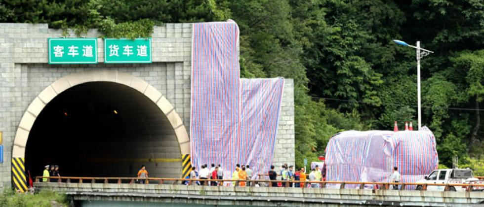 A damaged bus covered by tarp is seen outside the Qinling tunnel in Ankang in China's northern Shaanxi province on August 11, 2017.