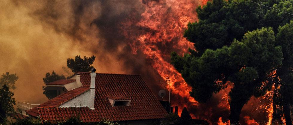 A house is threatened by a huge blaze during a wildfire in Kineta, near Athens, on July 23, 2018. Valerie Gache/AFP