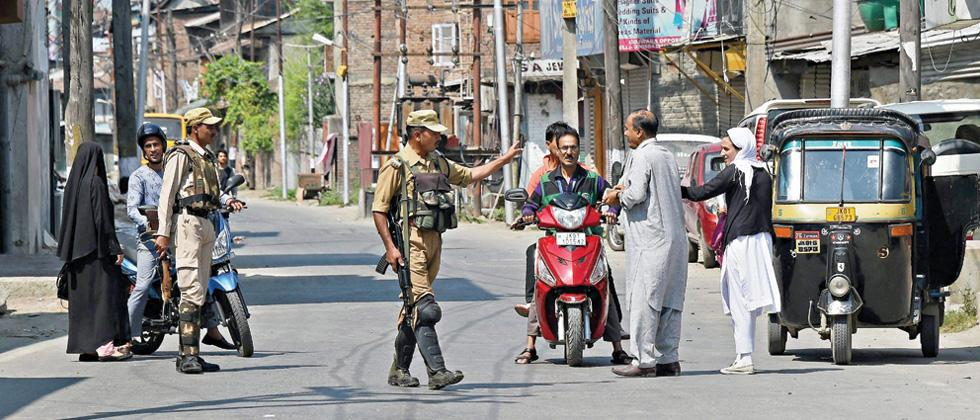 Security jawans checking the identity cards of commuters during restrictions in Srinagar on Tuesday, imposed in view of a strike called by separatist groups against the arrest of 7 separatist leaders by NIA.