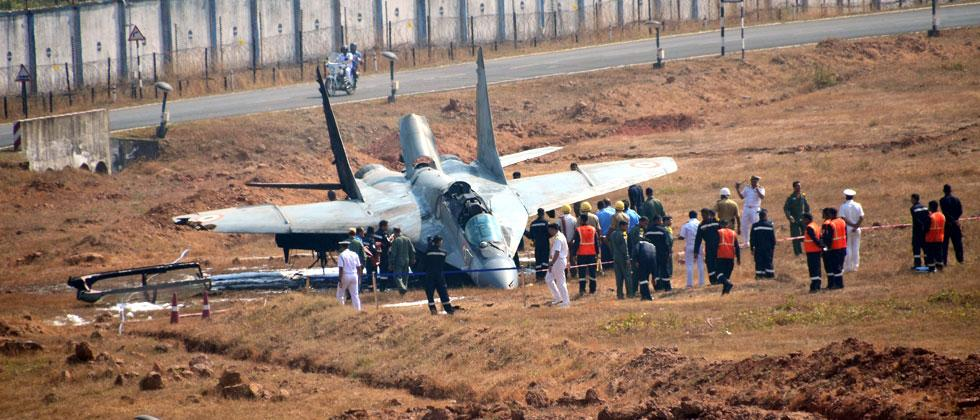 Security personnel standing near the MiG-29 K fighter jet of the navy which overshot the runway and crashed at Dabolim Airport in Goa on Wednesday. PTI Photo