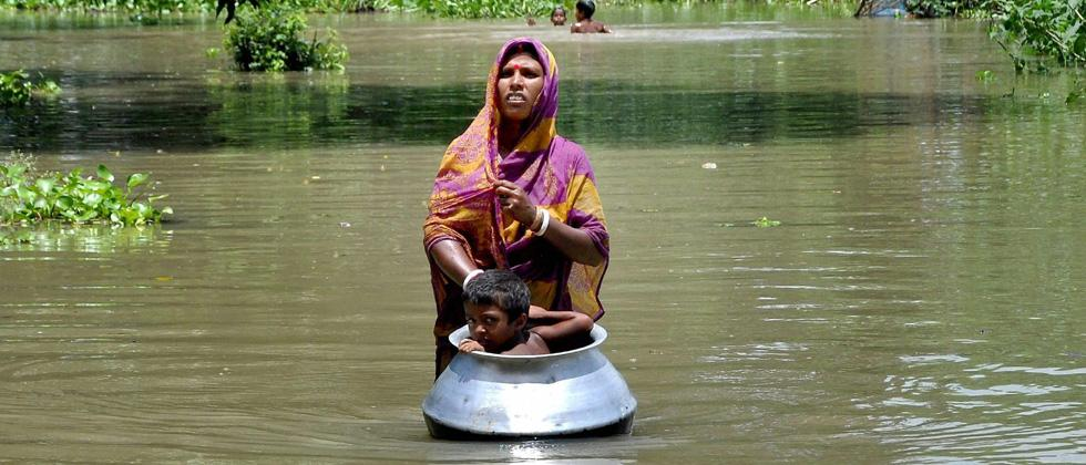 A woman with her child, in a utensil, moves to a safer place from the flood affected Khanamukh village in Morigoan, Assam on Wednesday. PTI Photo