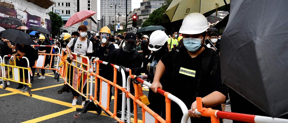 Protesters set up improvised barricades near The Peninsula hotel (back centre L) in the high-end shopping district of Tsim Sha Tsui in Hong Kong on Friday.