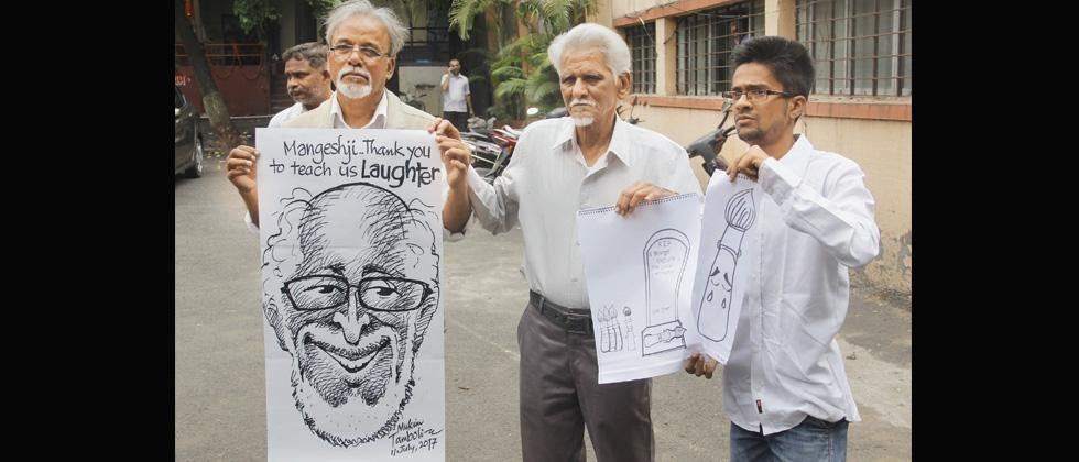 City cartoonists and admirers of veteran cartoonist Mangesh Tendulkar hold sketches dedicated to him outside Vaikunth crematorium in Navi Peth on Tuesday.  Tendulkar passed away at a private hospital in the city after a brief illness on Monday. (Pic: Vaib