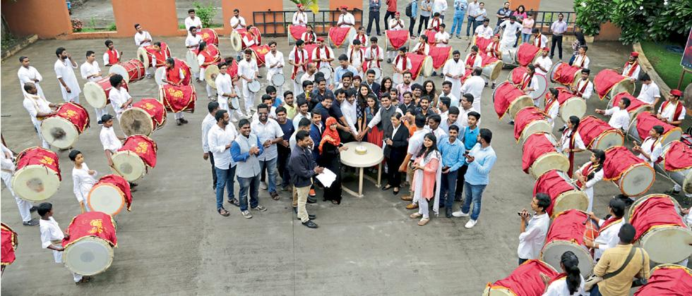 Team members of YIN along with Rucha Shrikhande and Rutuja Limaye cut the cake amidst the dhol-tasha procession at Sakal International Learning Centre on Saturday.
