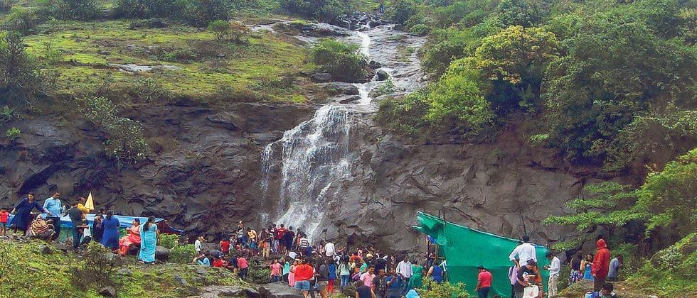 Tourists frolick near a waterfall in Lonavla on Sunday.