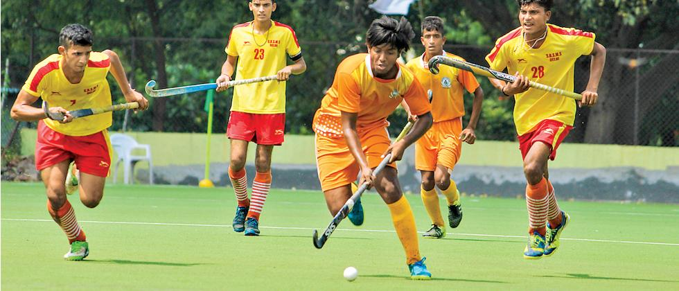 A player from SNBP Academy (in orange) controls the ball during their match against SBBS at Balewadi Sports Complex.