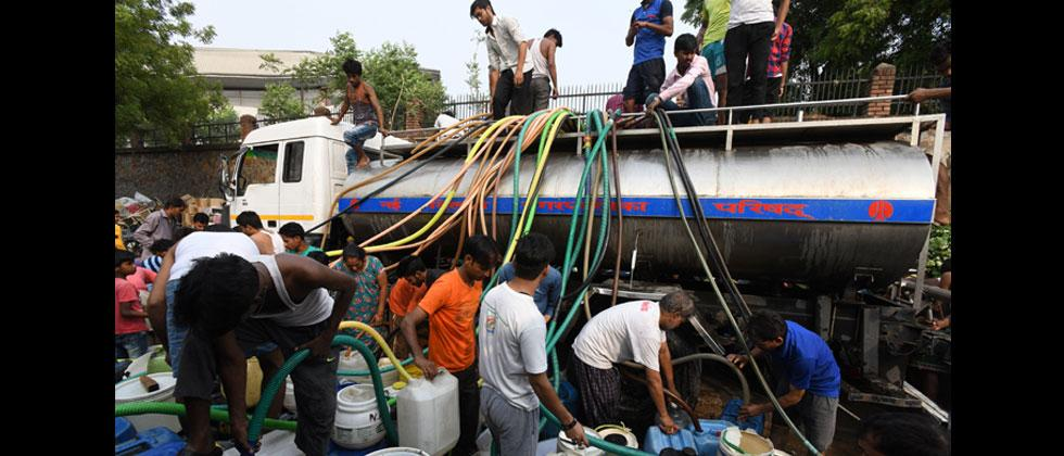Indian residents use hoses to fill jerry cans with water from a distribution truck which arrives daily, in the low-income eastern neighbourhood of Sanjay camp in New Delhi. Dominique Faget/AFP