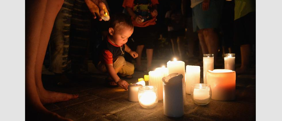 A child places a candle down during a evening candlelight prayer vigil at Life Christian Center Church on Friday in Branson Missouri.