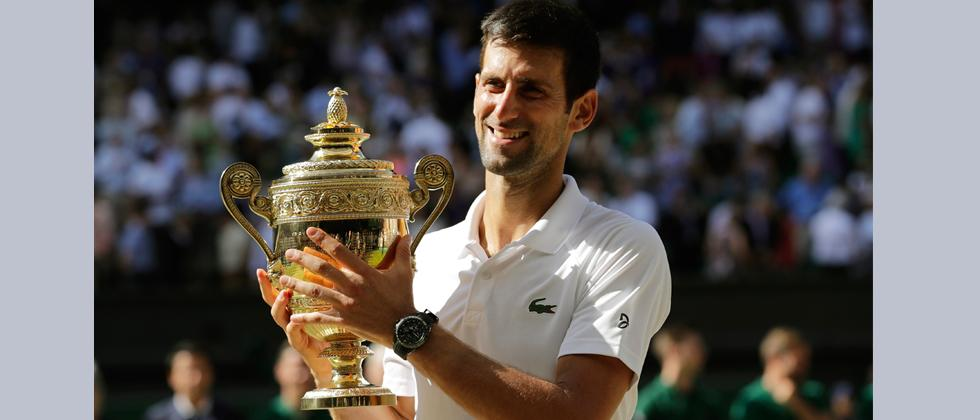Novak Djokovic of Serbia holds the trophy after defeating Kevin Anderson of South Africa in the men's singles final match at the Wimbledon Tennis Championships in London on Sunday