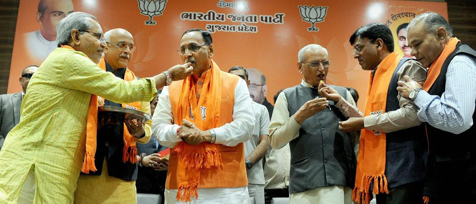 BJP leaders offering sweets to Gujarat chief minister Vijay Rupani after the party's win in the State assembly election
