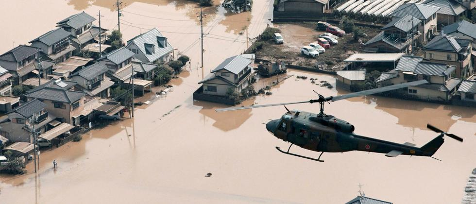 A helicopter flies over a flooded housing area in Kurashiki, Okayama prefecture, western Japan on Monday.