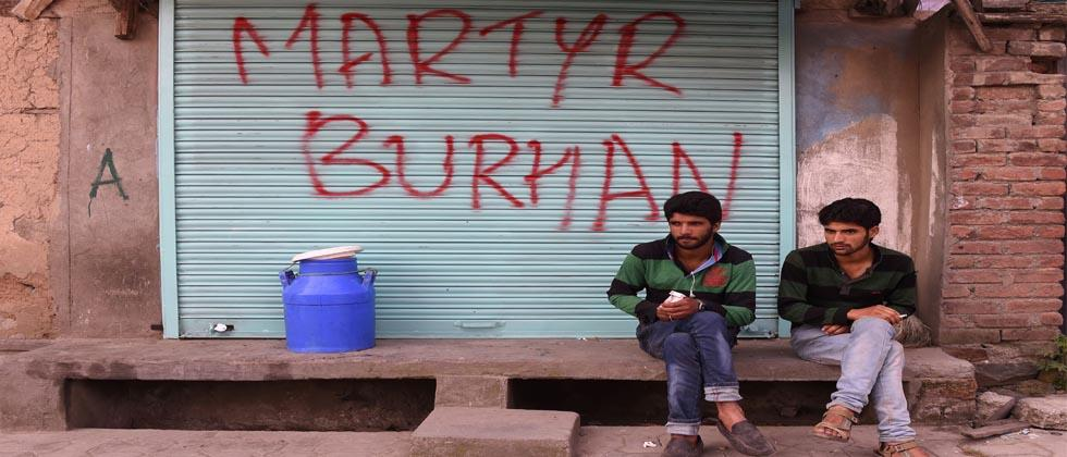 "Kashmiri men sit next to graffiti that reads ""Martyr Burhan"" in reference to the slain militant during a curfew in Srinagar on July 8, 2017."