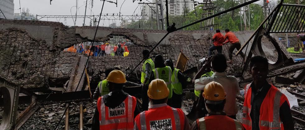 Railway and rescue workers gather around a site where a portion of a pedestrian footbridge collapsed over a railway track in Mumbai on Tuesday