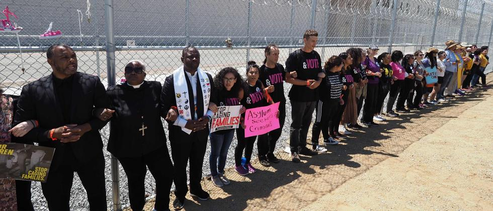 Protestors link arms after tying children's shoes and keys on the fence outside the Otay Mesa Detention Center during a demonstration against US immigration policy that separates children from parents, in San Diego, California on Saturday.