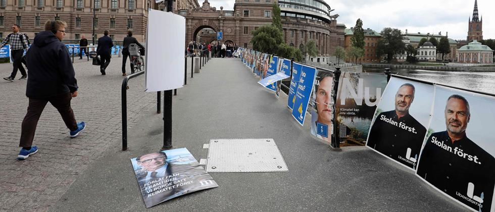People pass election posters near the Swedish parliament in Stockholm on Monday the day after general elections in Sweden.