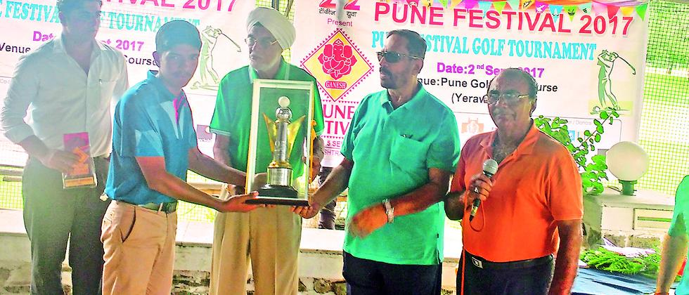 Pratik Nirmale (left) receives Pune Festival Golf trophy from Suresh Kalmadi (2nd from right), on Saturday. Also seen is Poona Club Golf Captain Narotam Chowdhary.