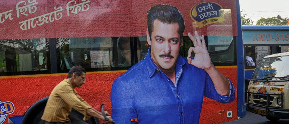 A cyclist rides past a bus with a huge poster of actor Salman Khan, in Kolkata on Thursday. Jodhpur court today sentenced Salman Khan to five years in jail in the 1998 blackbuck poaching case. PTI Photo