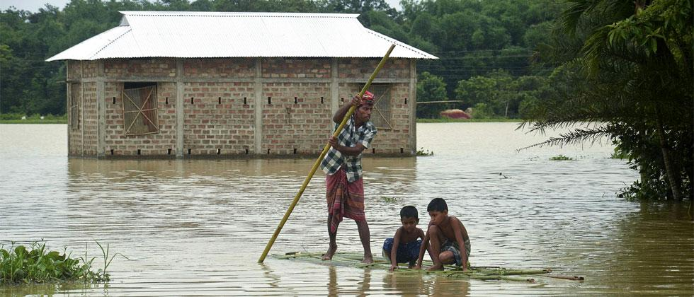 Indian villagers cross flooded area on a bamboo raft at a village in Dharmanagar on June 13, 2018, in the northeastern state of Tripura. Lovely Ghosh/AFP