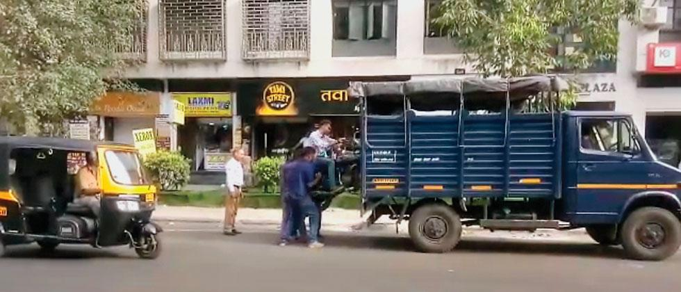 A video grab shows a man being lifted along with his bike and put in the tempo