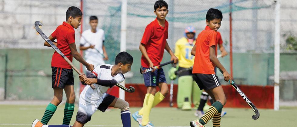 A player of Netaji Subhashchandra Bose Boy's Military School (in white) in action against  Shree Anantrao Kulkarni English Medium School, Narayangaon, at Major Dhyan Chand Poligras Stadium in Pimpri