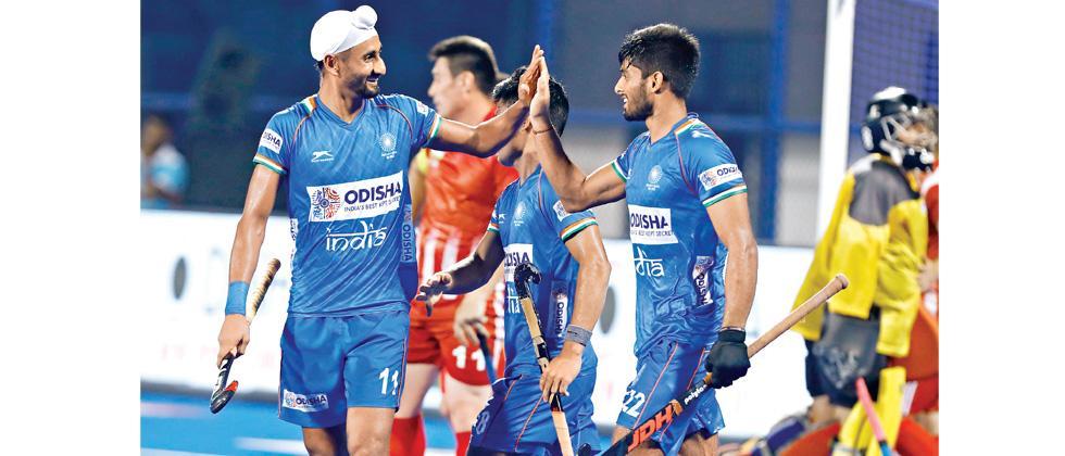 Mandeep Singh (left) celebrates scoring a goal with Varun Kumar.