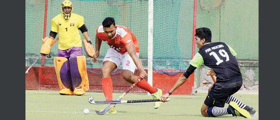 A player from PC XI (red) hits the ball during thier match against Pune Magician in a 9-A-side Hockey Tournament at Major Dhyanchand Poligras Stadium in Pimpri on Monday