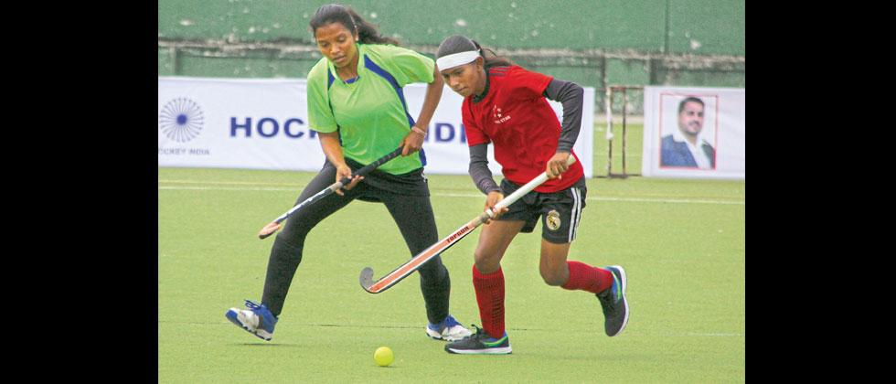 A player from 5 Star (red) hits the ball during their match against Priyadarshini Sports Centre at the Major Dhyan Chand Hockey Stadium, Nehrunagar-Pimpri on Thursday