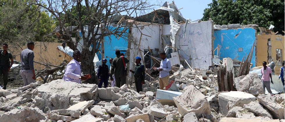 People stand in the rubble at a car suicide car bomb scene on Friday in Mogadishu. - A suicide car bomb killed three security guards and injured several more people in the heart of the Somali capital Mogadishu.