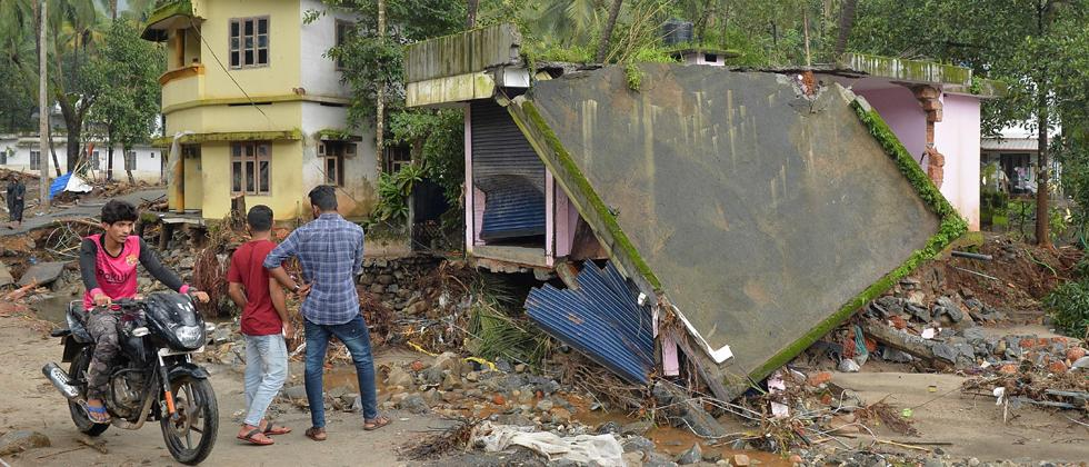 People look at houses destroyed by a landslide at Kannapanakundu village, about 422 km north of Trivandrum, in the south Indian state of Kerala on Saturday.