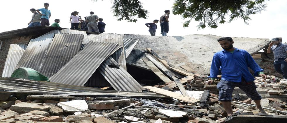 Kashmiri villagers walk through a damaged house where two militants were killed during a gunfight with government forces in the Hakripora village of Pulwama on August 1, 2017.