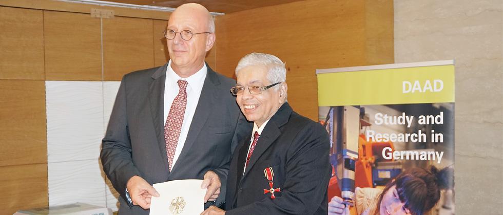 Dr Jurgen Mohard presenting the award to Dr Arvind Natu.
